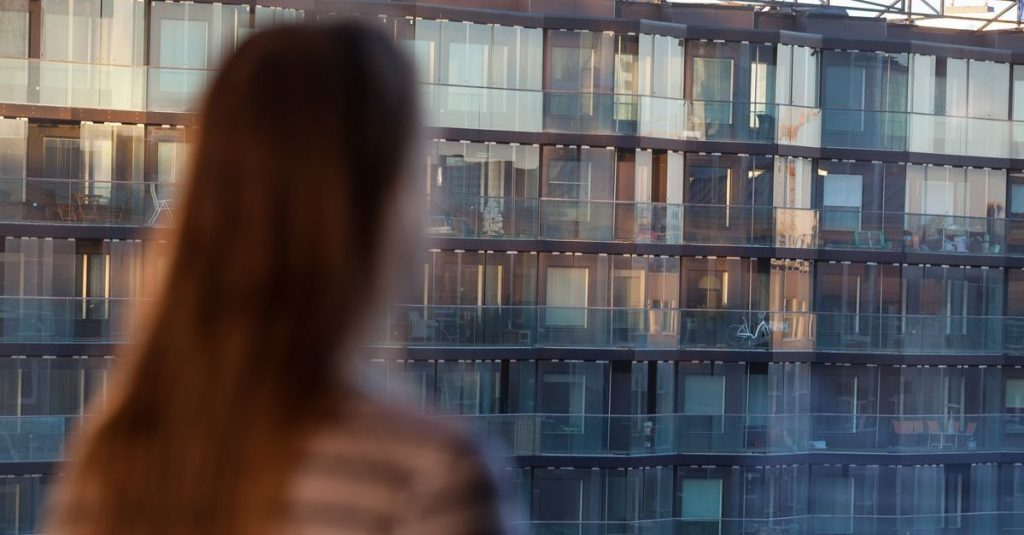Woman looking at an apartment block