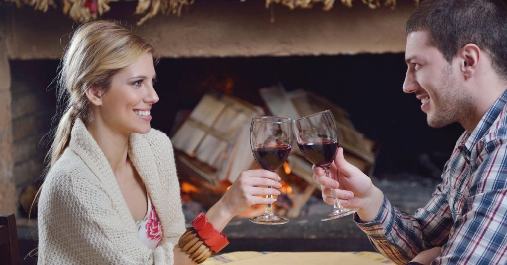 Young romantic couple sitting and relaxing in front of fireplace